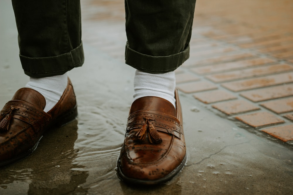 person in brown leather shoes