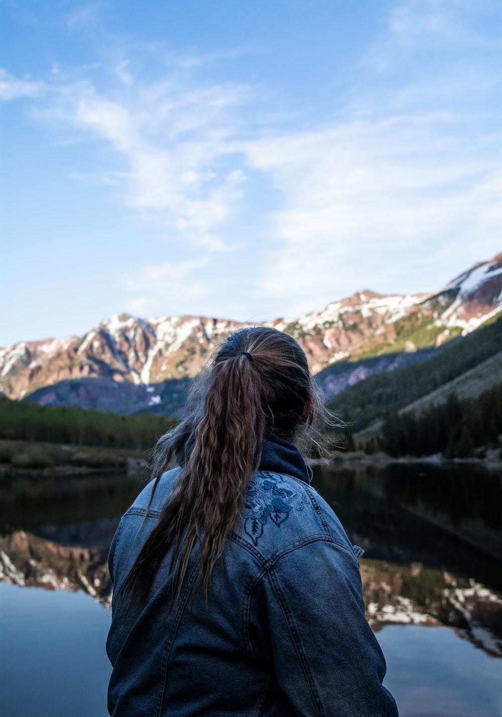 woman in blue denim jacket standing near lake during daytime
