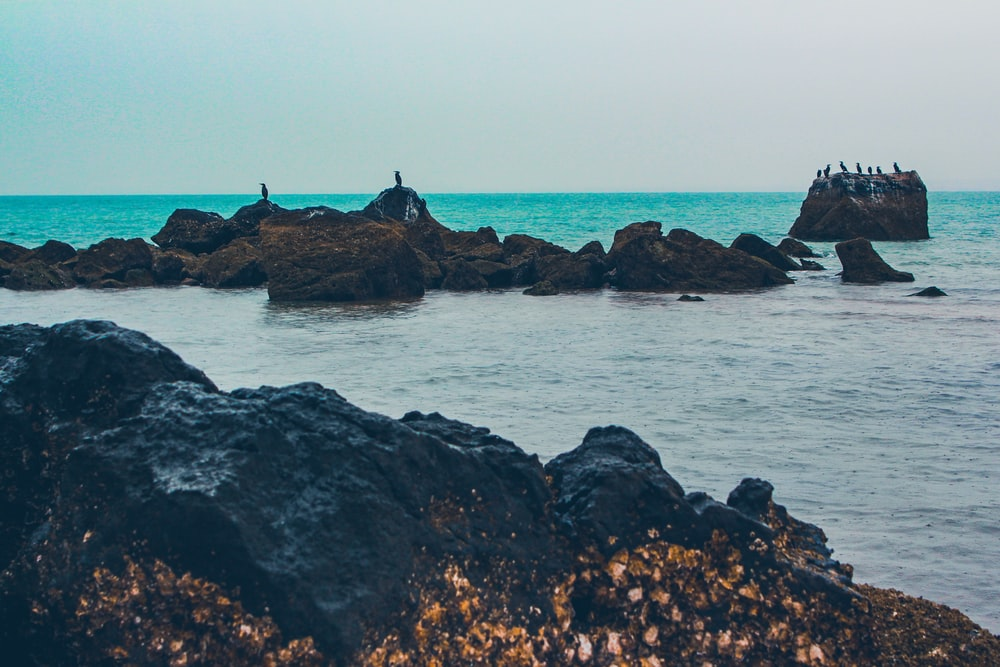 person standing on rock formation in the middle of sea during daytime