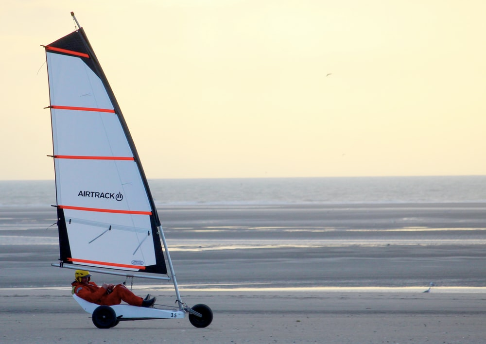 red and white sailboat on sea during daytime