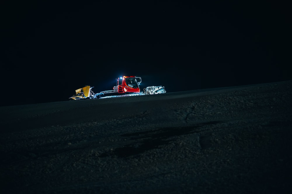 red and white formula 1 on snow covered ground during night time