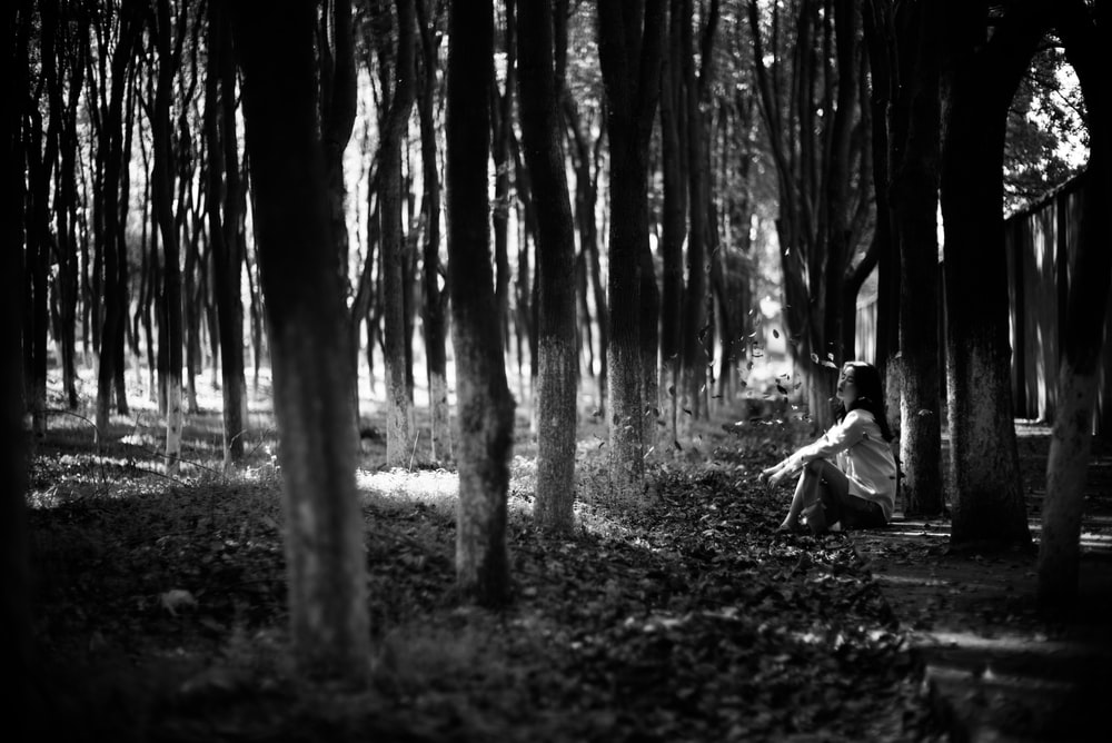grayscale photo of man sitting on ground surrounded by trees