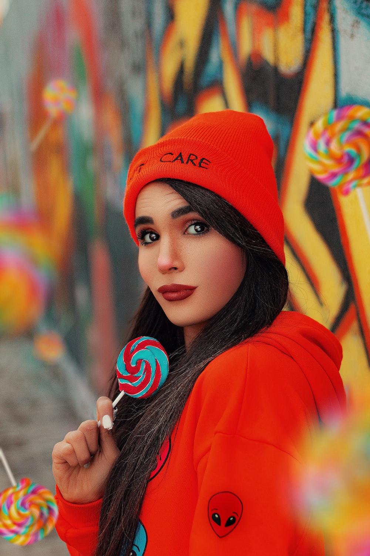 woman in orange knit cap and orange hoodie