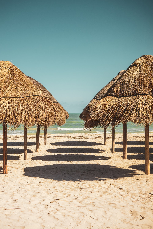 brown wooden nipa hut on beach during daytime