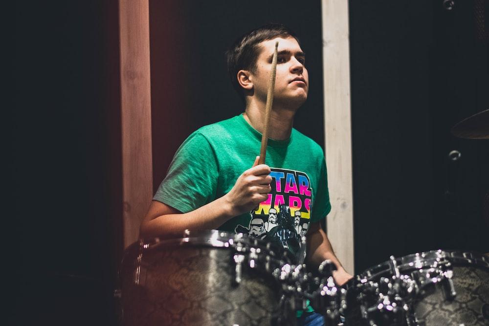 man in teal crew neck t-shirt playing drum