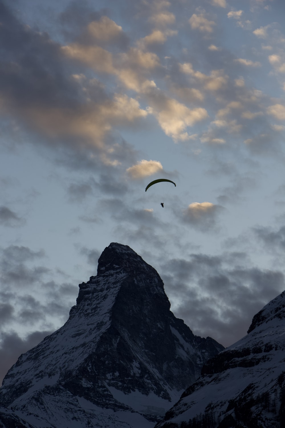 person in parachute over rocky mountain during daytime