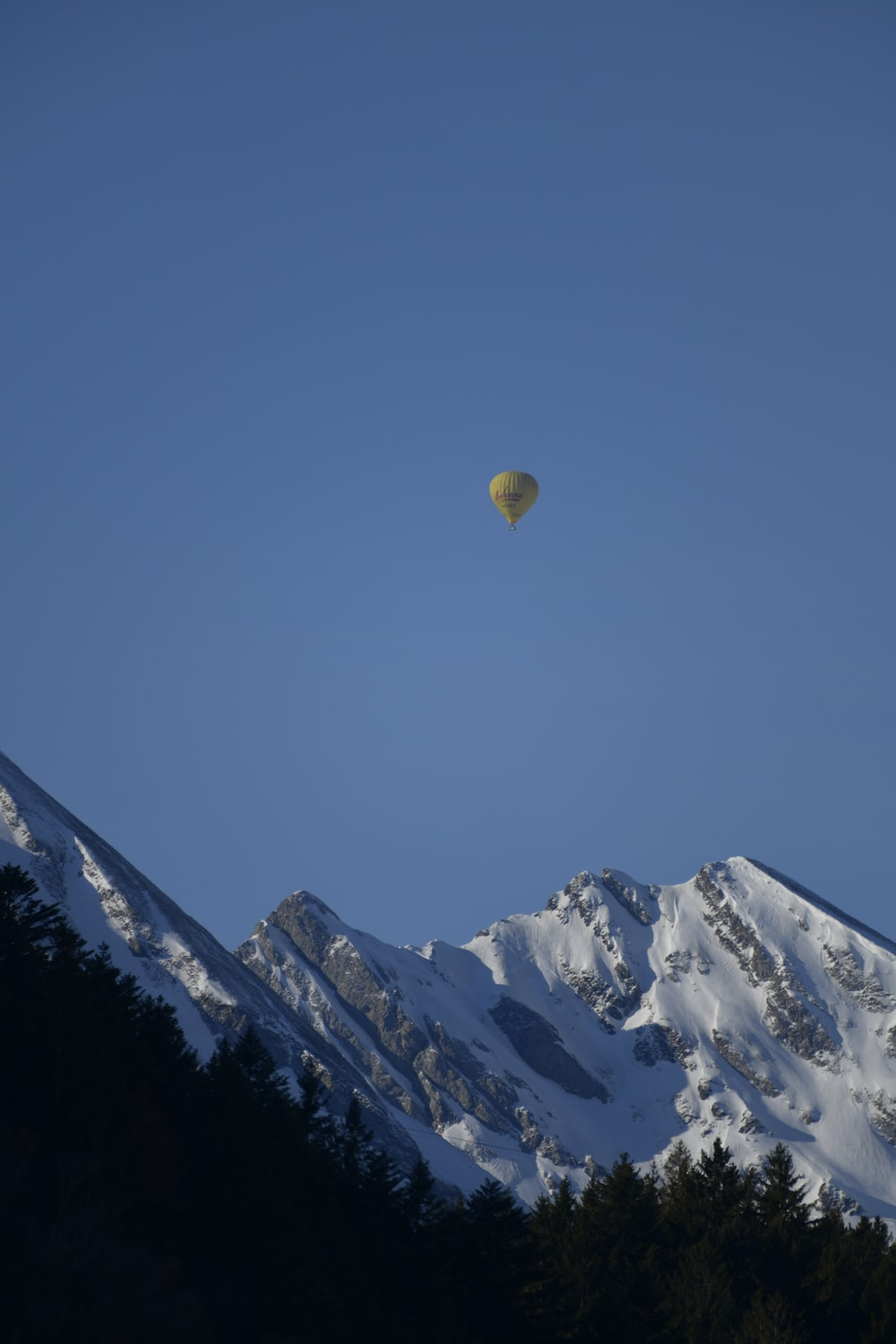 hot air balloon flying over snow covered mountain