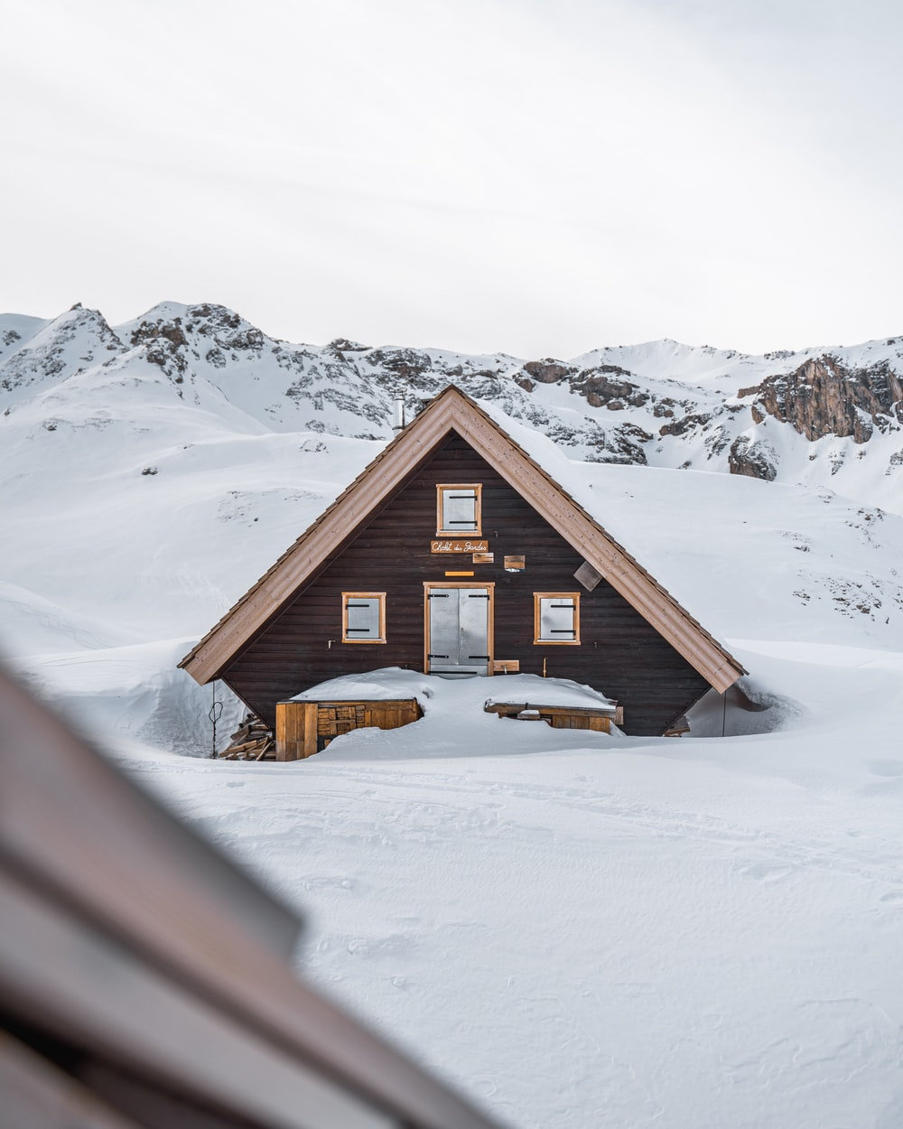 brown wooden house on snow covered ground