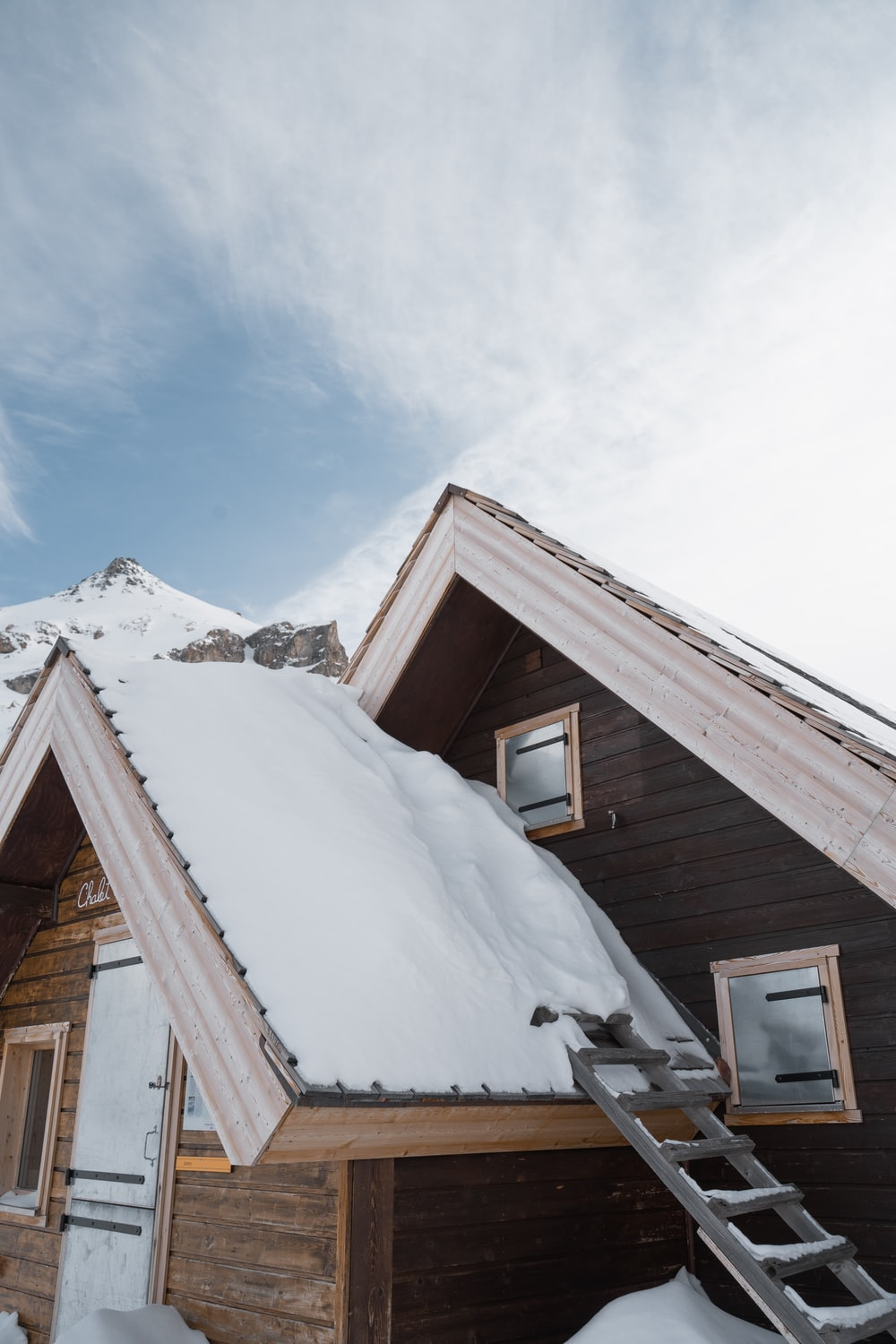 brown wooden house covered by snow during daytime