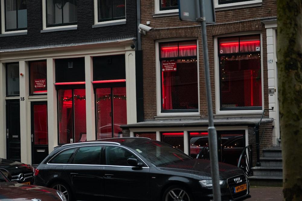 black sedan parked beside red building