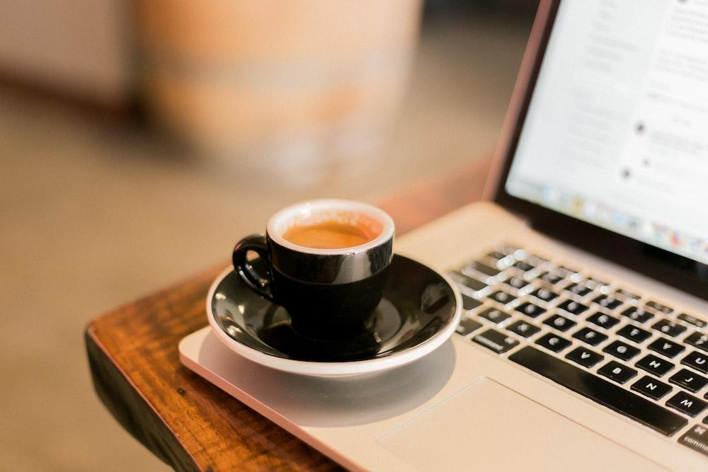 black ceramic cup on white ceramic saucer