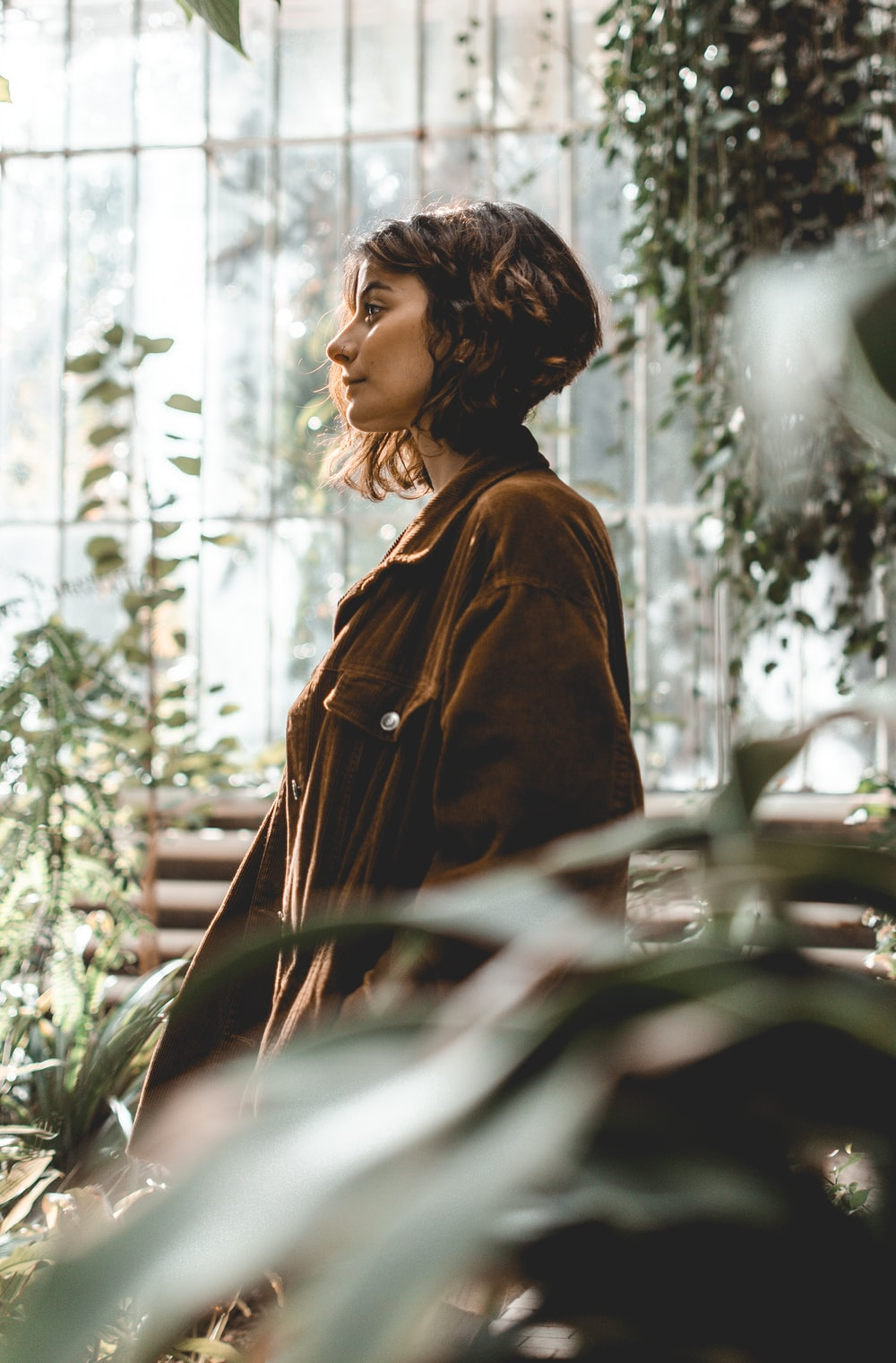 woman in brown leather jacket standing near green plants during daytime