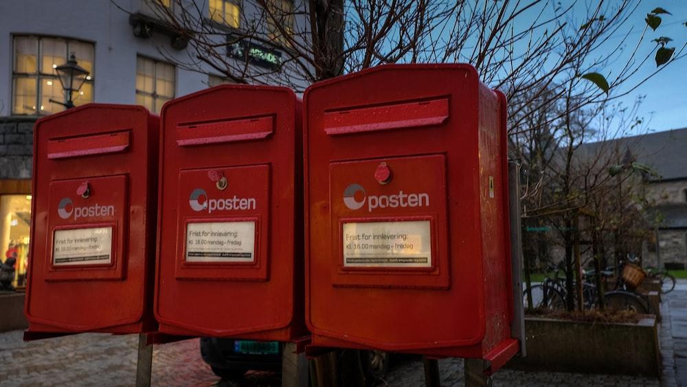 red mail box on sidewalk during daytime