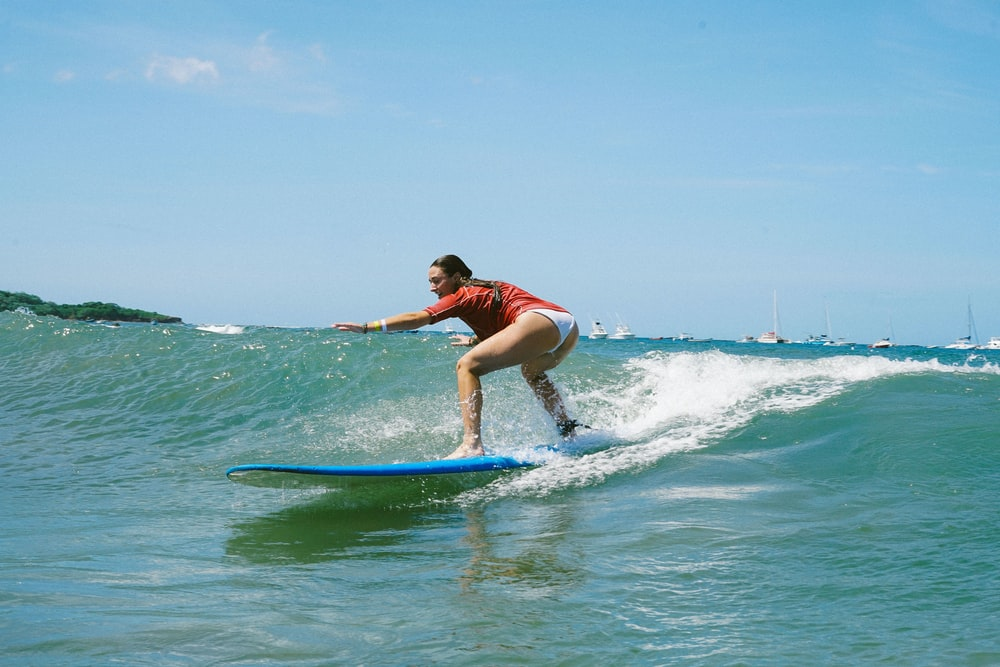 woman in blue and white wetsuit surfing on sea during daytime