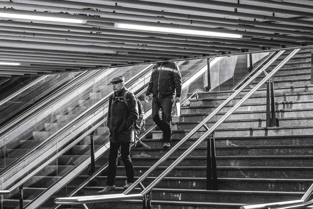 grayscale photo of man in jacket and pants walking down the stairs