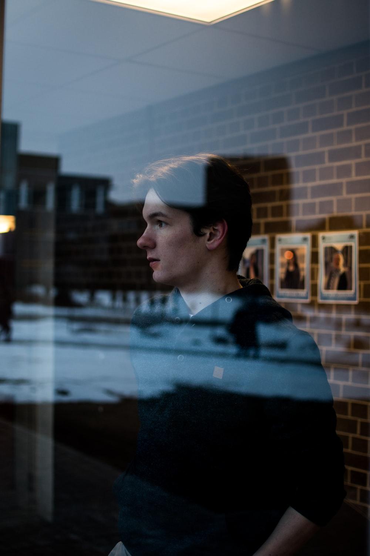 man in black sweater standing near glass window