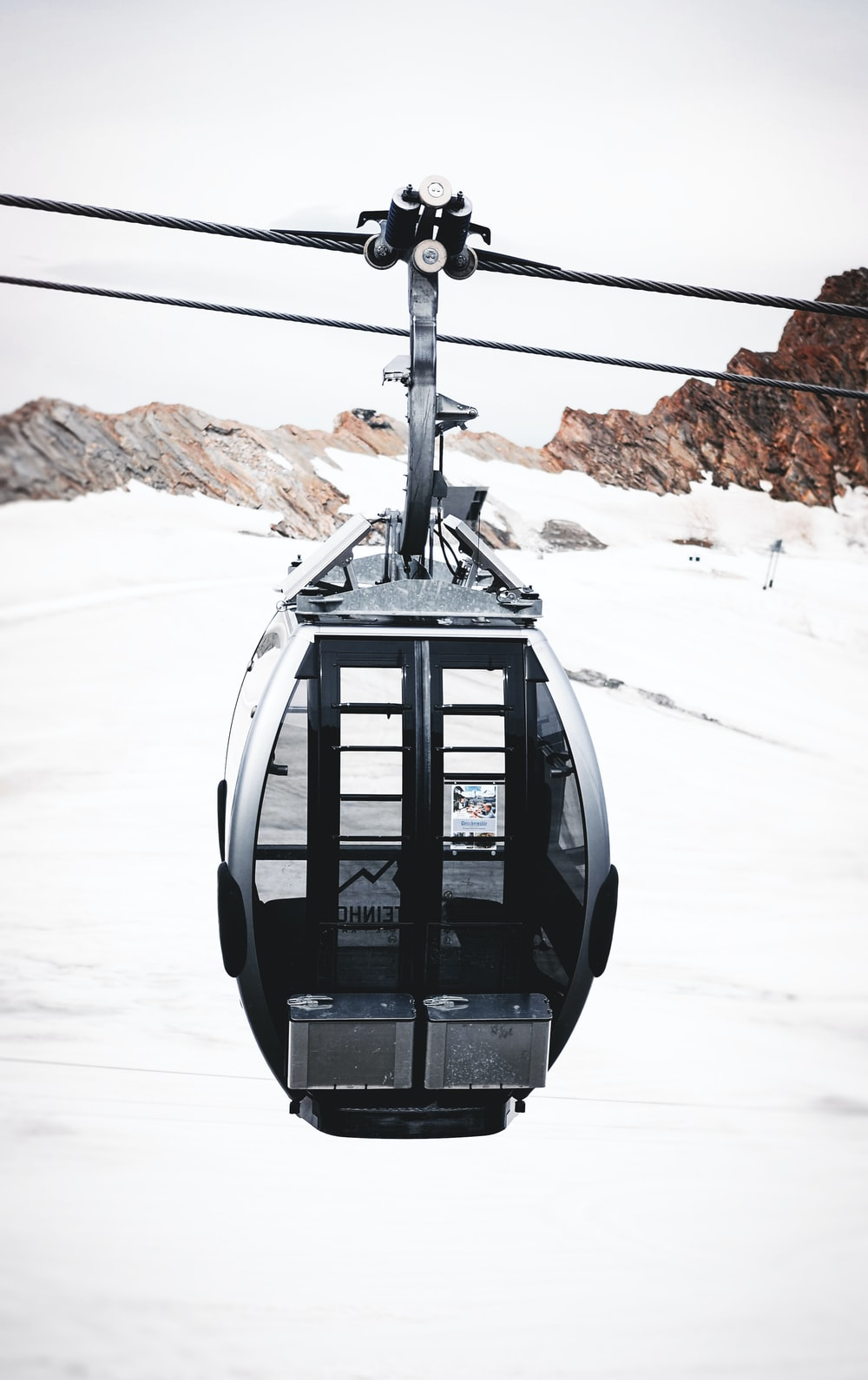 black cable car on snow covered ground during daytime