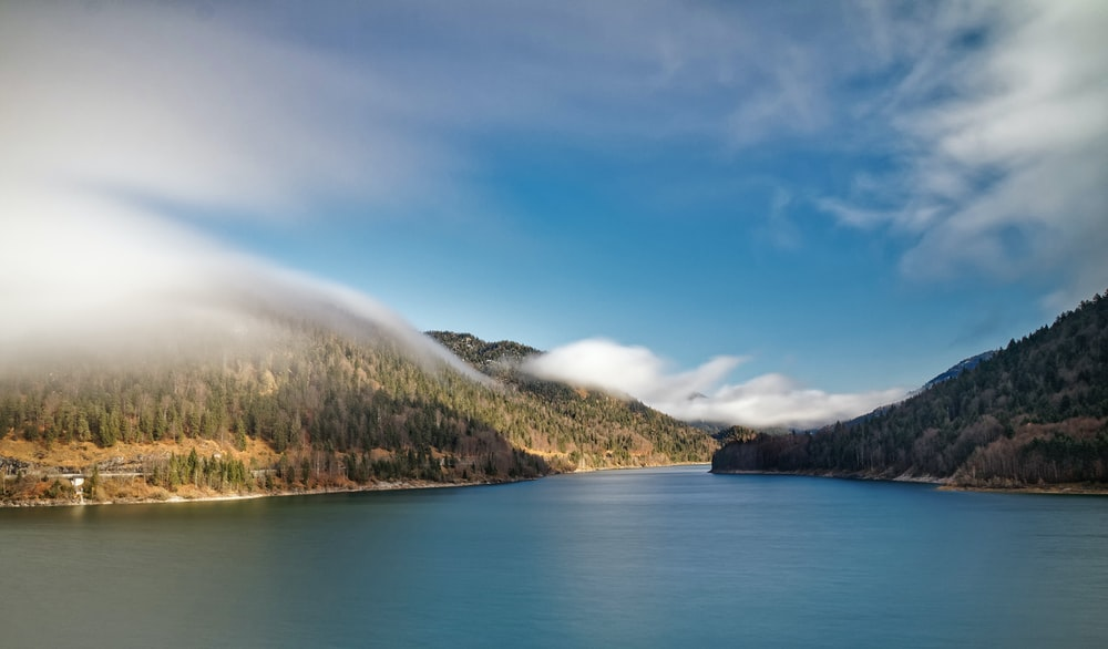 lake near green trees and mountain under blue sky during daytime
