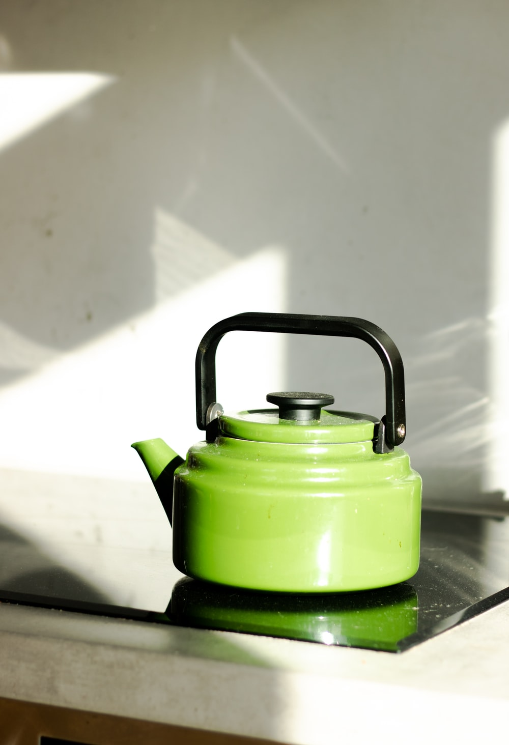 green and black kettle on brown wooden table