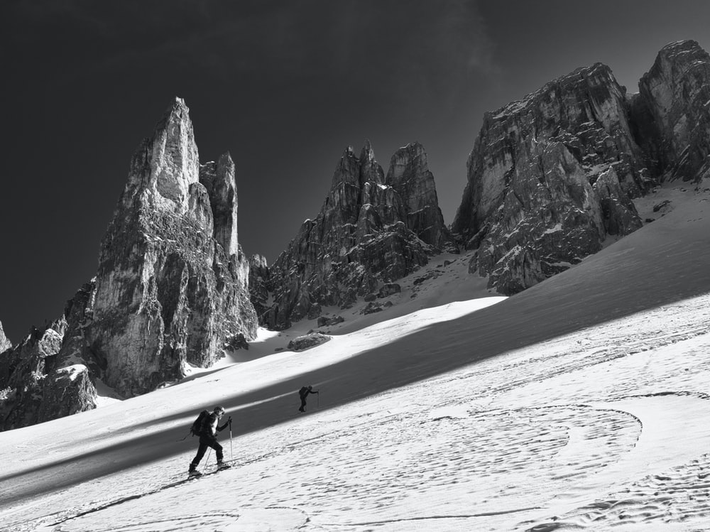 grayscale photo of man walking on snow covered field near rocky mountain