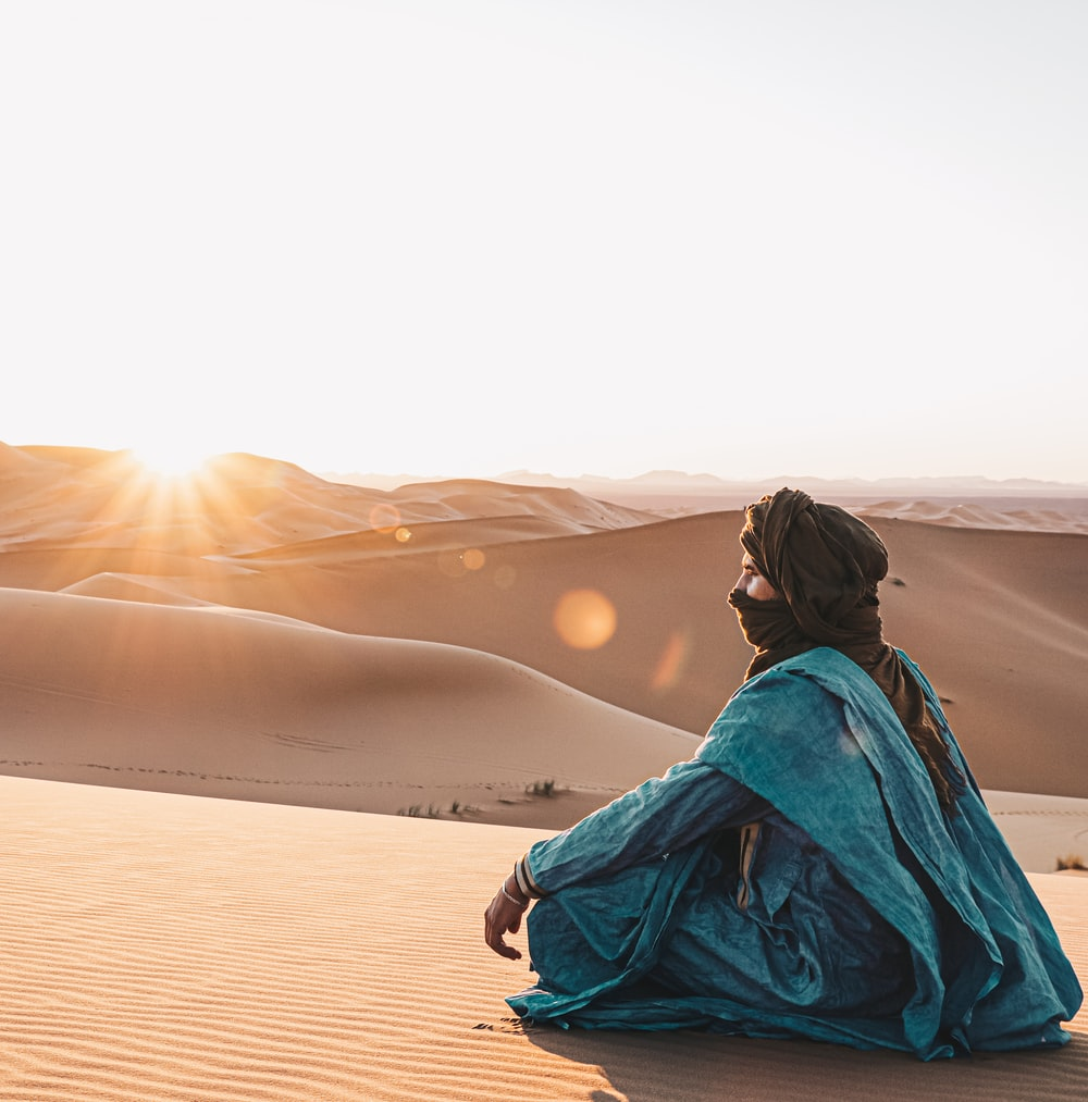 woman in blue hoodie sitting on sand during sunset
