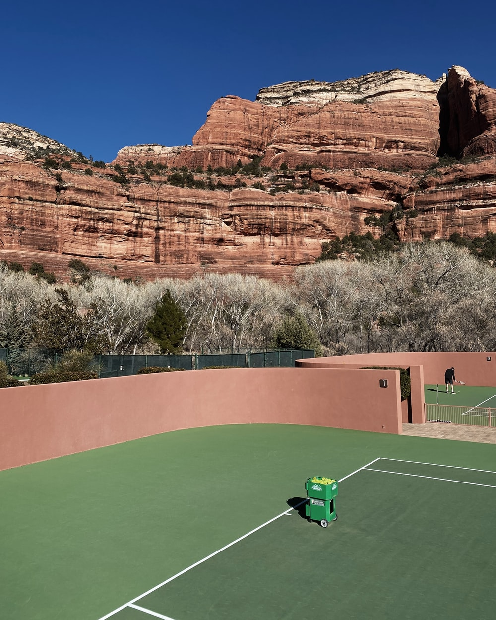green golf course near brown rock formation during daytime