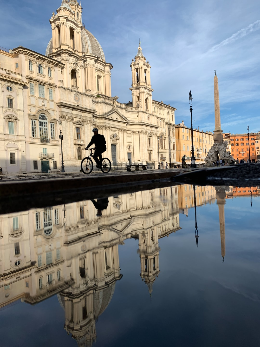 Piazza Navona with Sant'Agnese as the main scene with a reflection from a puddle on the ground.  There is a bike / bicyclist in the middle.  AMAZING! Sant'Agnese in Agone is a 17th-century Baroque church in Rome, Italy. It faces onto the Piazza Navona, one of the main urban spaces in the historic centre of the city and the site where the Early Christian Saint Agnes was martyred in the ancient Stadium of Domitian. Construction began in 1652 under the architects Girolamo Rainaldi and his son Carlo Rainaldi. After numerous quarrels, the other main architect involved was Francesco Borromini.[1]