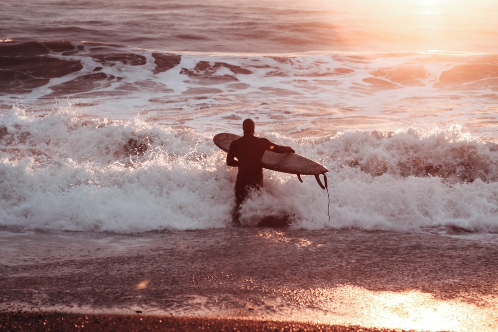 man in black wet suit holding surfboard on beach during daytime