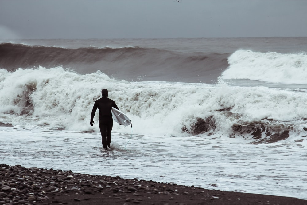man in black wet suit holding white surfboard walking on beach during daytime