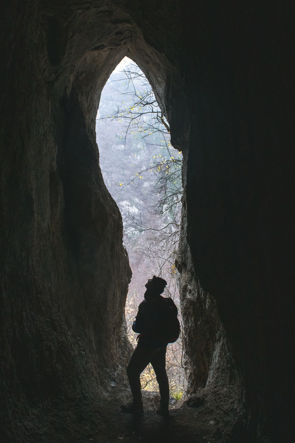 silhouette of man in cave during daytime