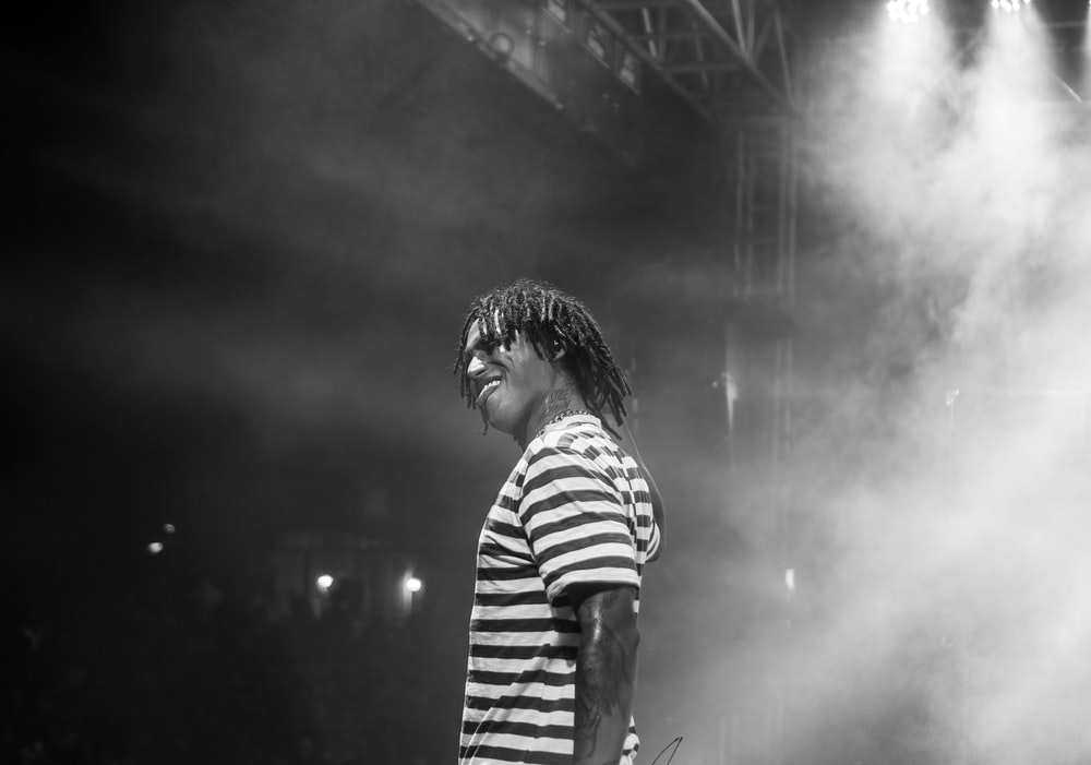 man in striped shirt standing in front of stage