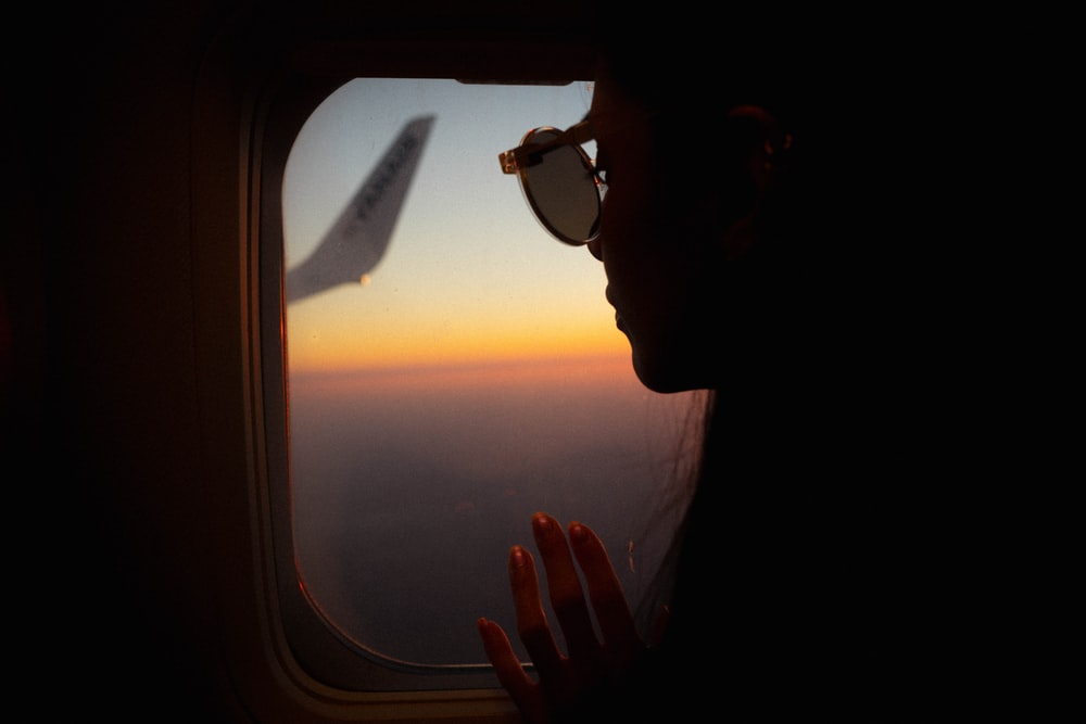 man in black sunglasses looking at the airplane window during sunset