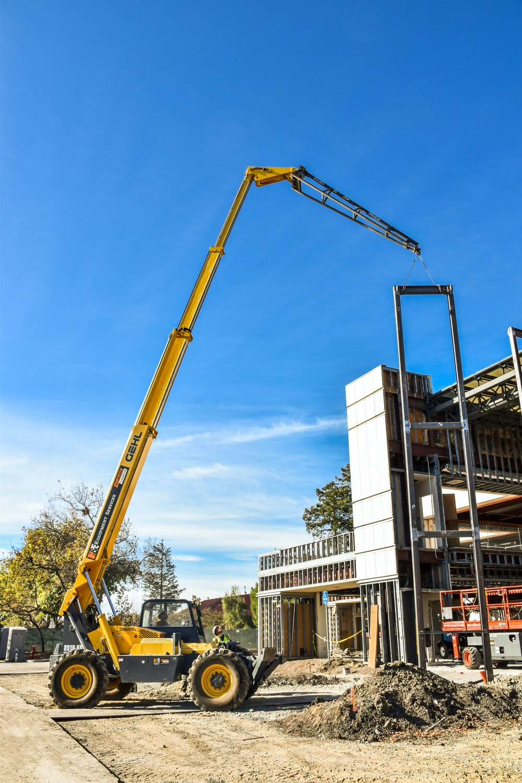 yellow crane near white building during daytime