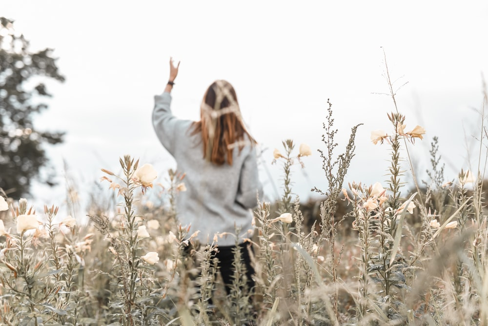 woman in white sweater standing on brown grass field during daytime