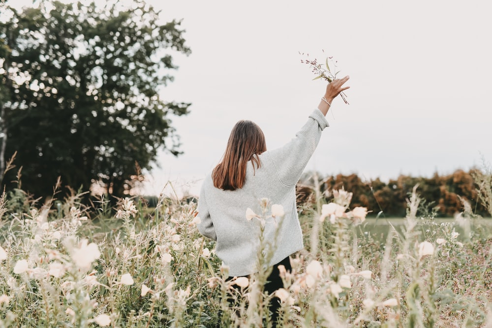 woman in white sweater standing on white flower field during daytime