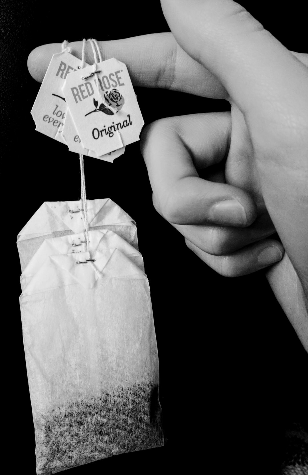 Black and White focus of person holding red rose tea bags