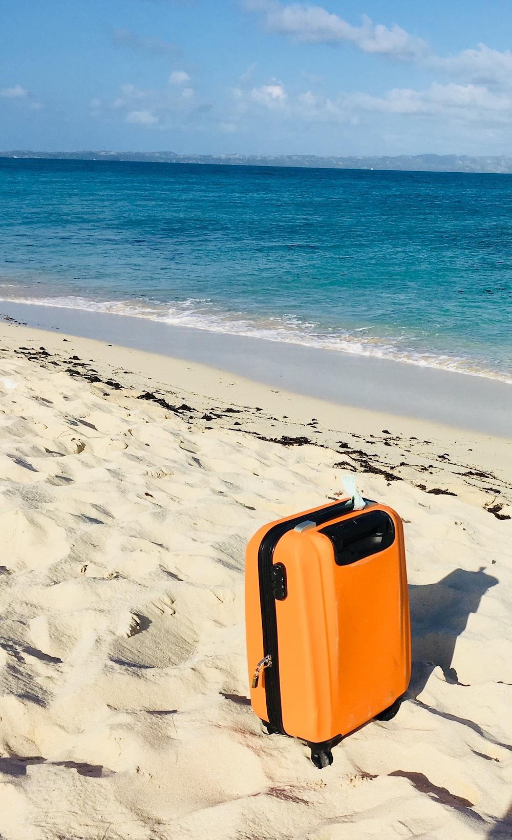 orange and white luggage bag on beach