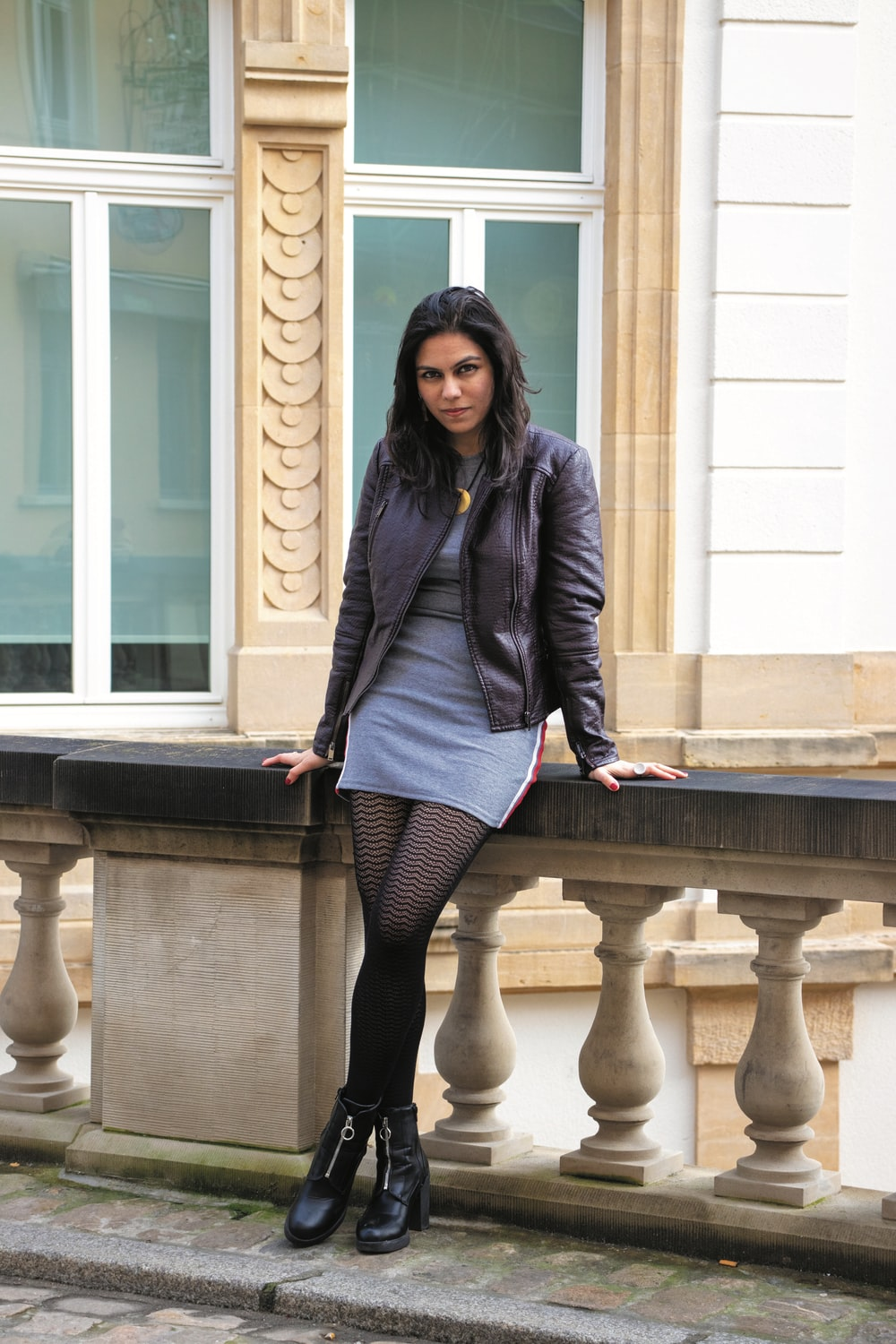 woman in blue blazer and black skirt standing on brown concrete stairs