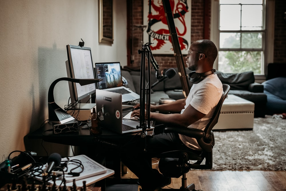 man in white t-shirt sitting on black office rolling chair