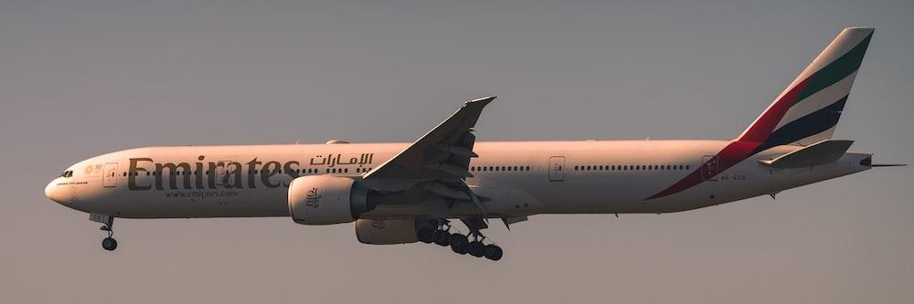 white passenger plane in mid air during daytime