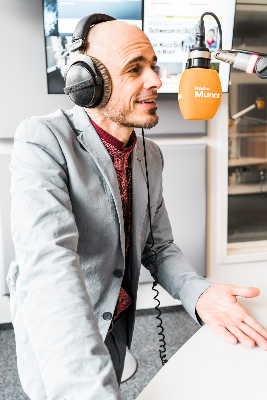 man in gray suit jacket wearing black headphones