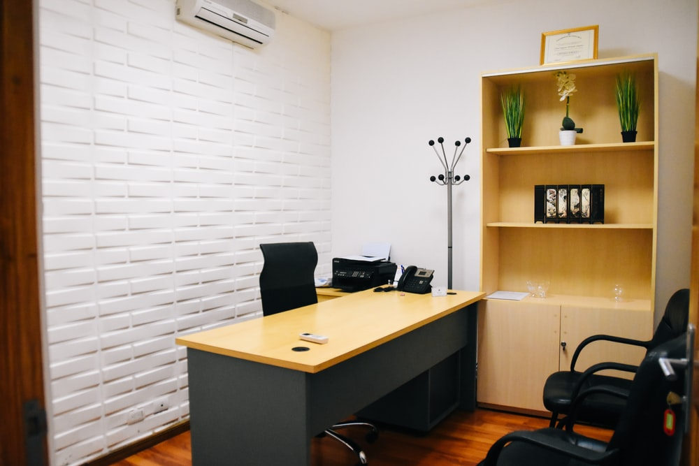 black office rolling chair beside brown wooden table