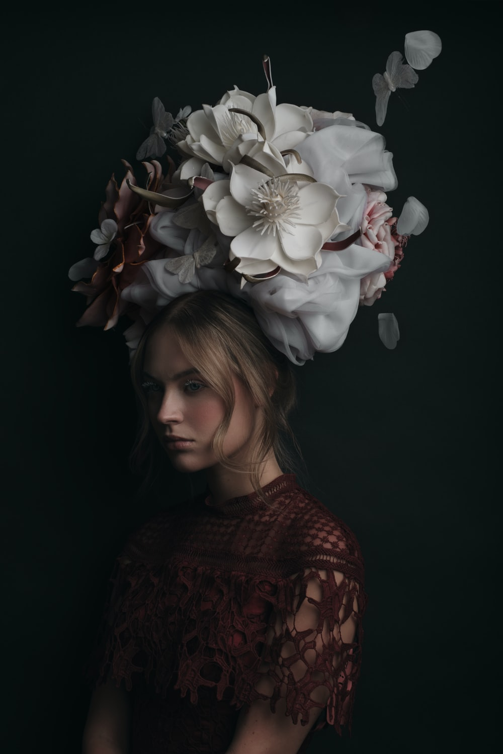 woman in red and black sweater with white flower on head