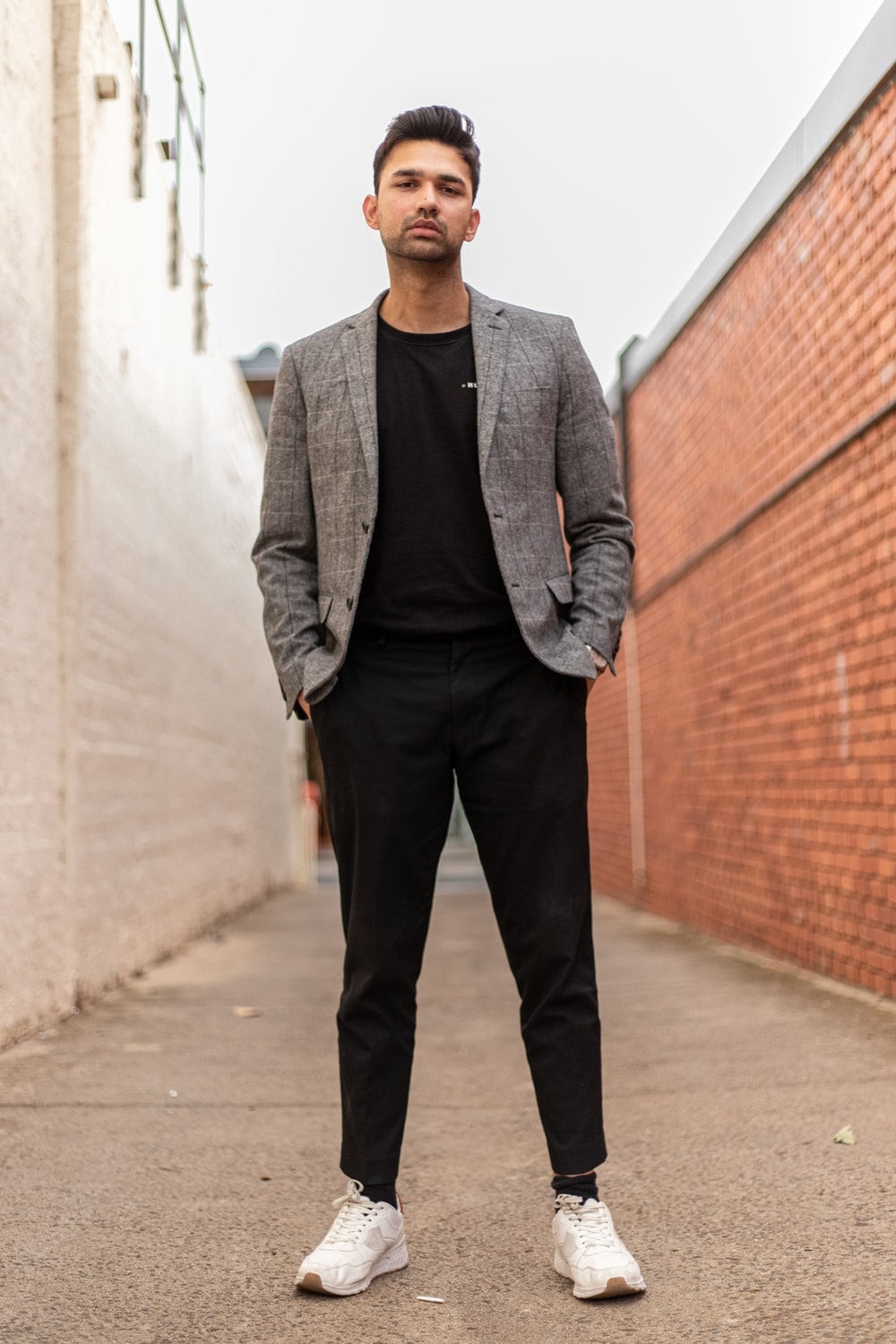 man in gray suit jacket and black pants standing on brown brick wall during daytime