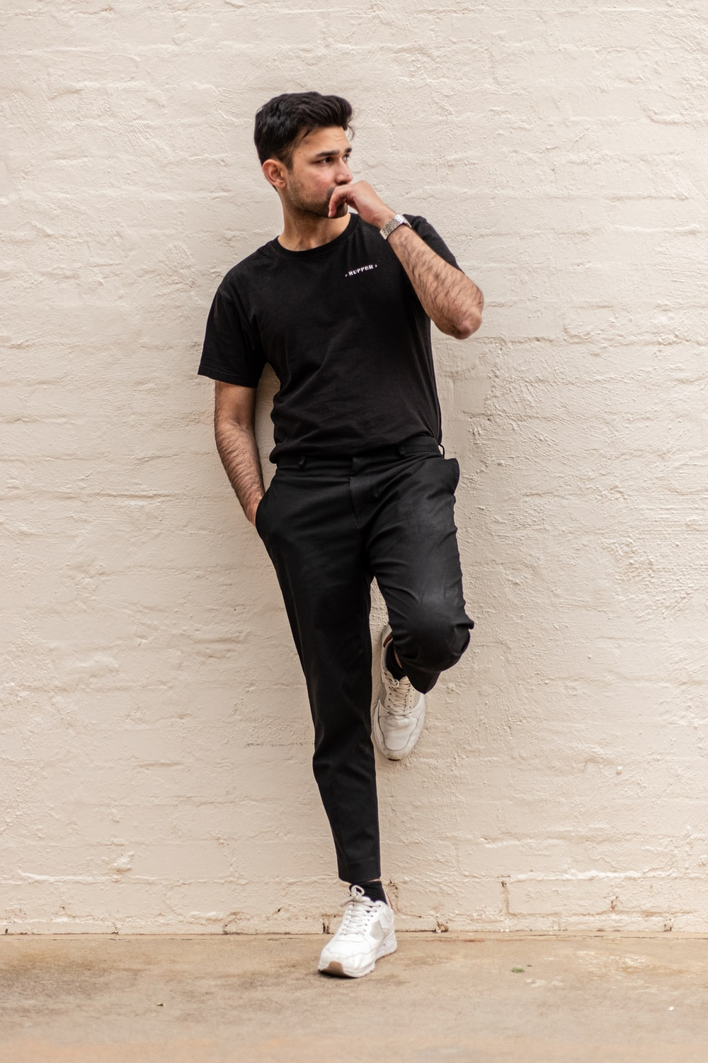 man in black crew neck t-shirt and blue denim jeans leaning on white wall
