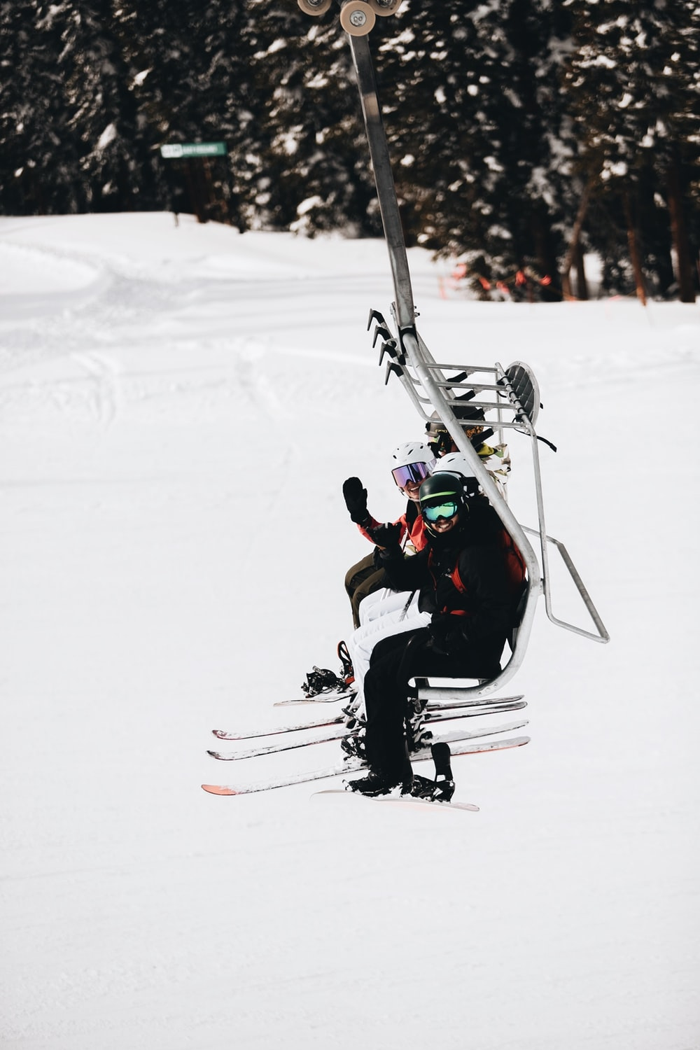 man in black jacket and red pants riding ski blades on snow covered ground during daytime