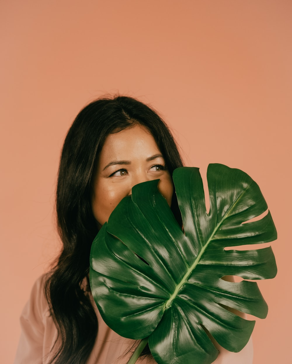 woman in white shirt covering her mouth with green leaf