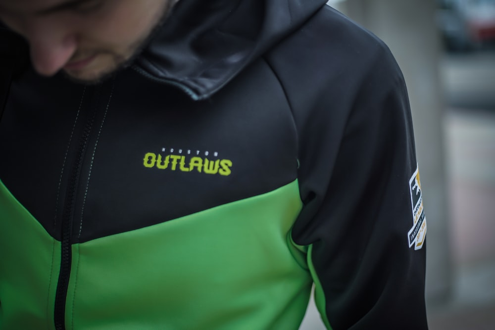 man in black and green adidas hoodie