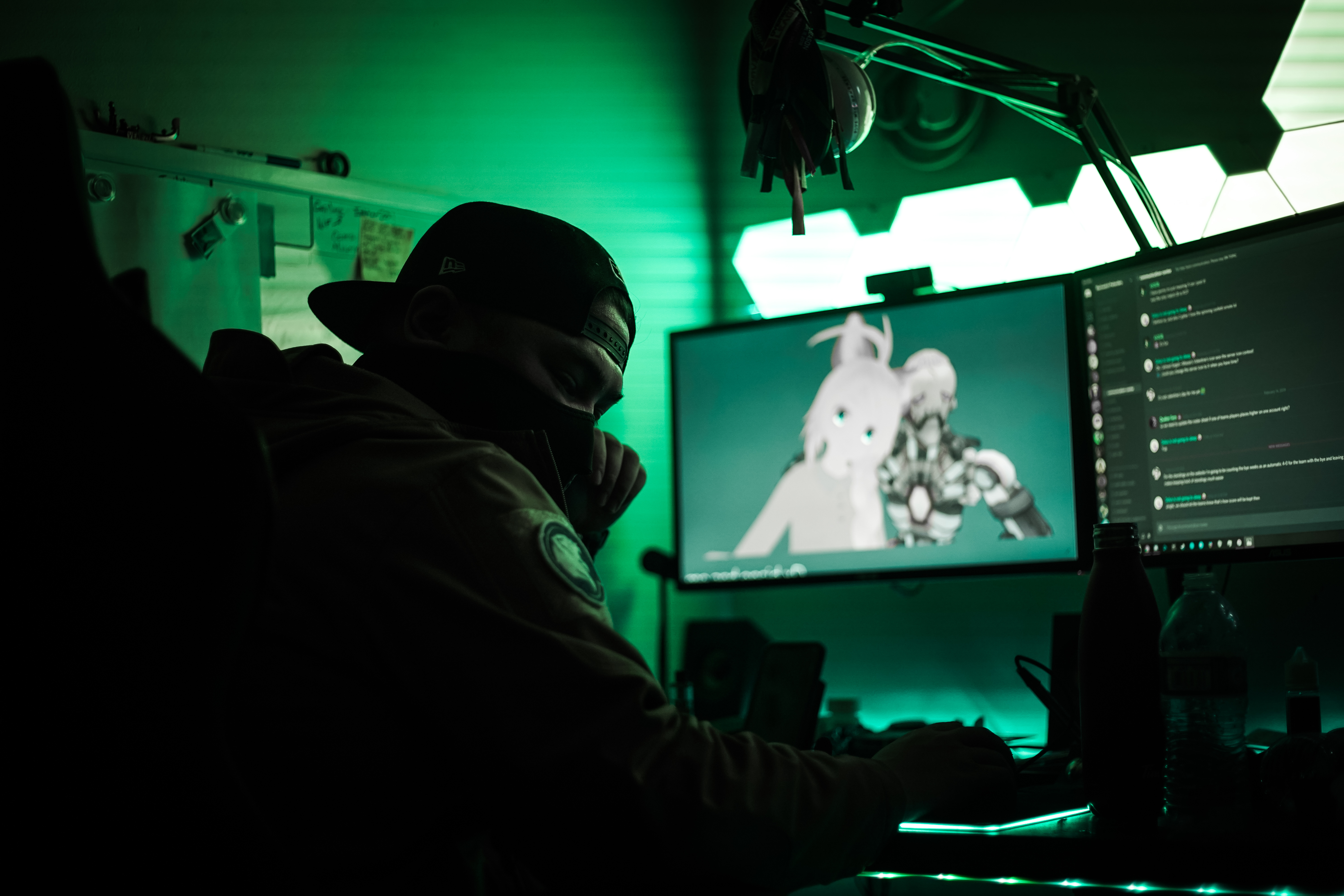 Gamer wearing a mask looks away from glowing computer and light panels.