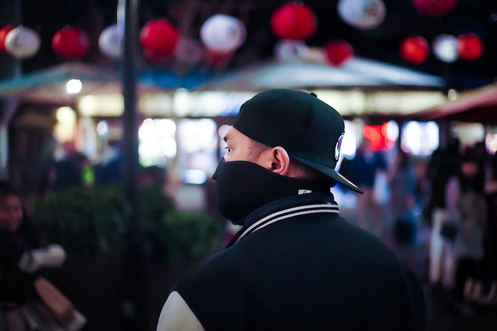 man in black and white shirt wearing black cap